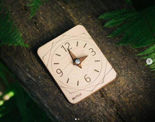 Elegants koka stāvvietas pulkstenis ar ādas apdari.